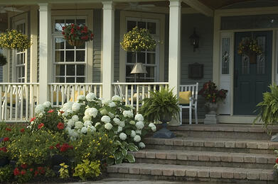 Glow of summer sunrise on front porch of suburban house