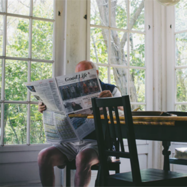 Man reading newspaper at kitchen table