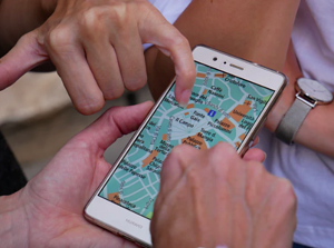 people pointing to location on mobile map