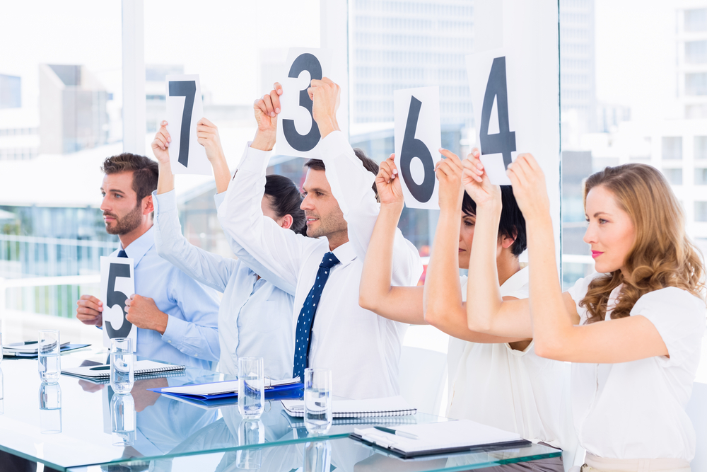 Side view of a group of panel judges holding score signs in a bright office