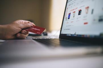 making an online purchase with credit card in hand and laptop open