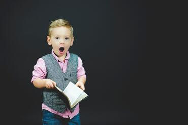 child holding book with a surprised look